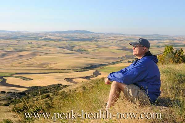 Mens health - hiker sitting on hill enjoying the view.